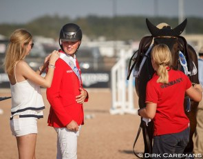 Friederike Hahn attaching the champion's sash on boyfriend Maurice Tebbel at the 2018 World Equestrian Games :: Photo © Dirk Caremans