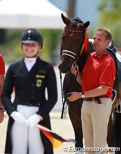 Dad Johannes Westendarp holds Der Prinz while daughter Alexa gets ready to mount the podium to receive the team gold medal