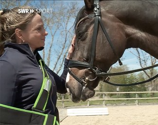 Dorothee Schneider with her arm in a sling, patting Faustus :: Photo SWR sport